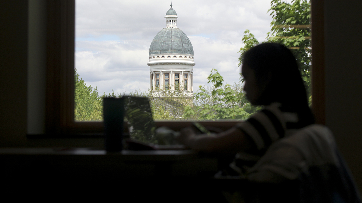 student studying in front of old main