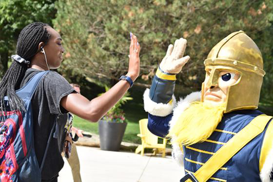 Gus gives a student a high-five.